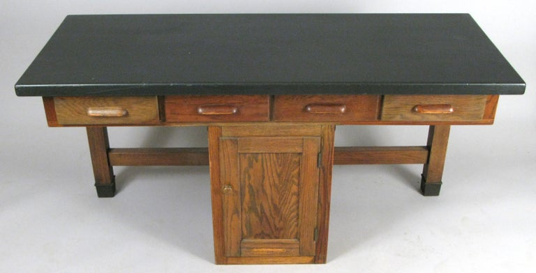 An antique 1940s oak lab desk table by Welch, with a center cabinet and four drawers across the top. the desk has seating spaces on either side of the center cabinet, with a black finished oak top.