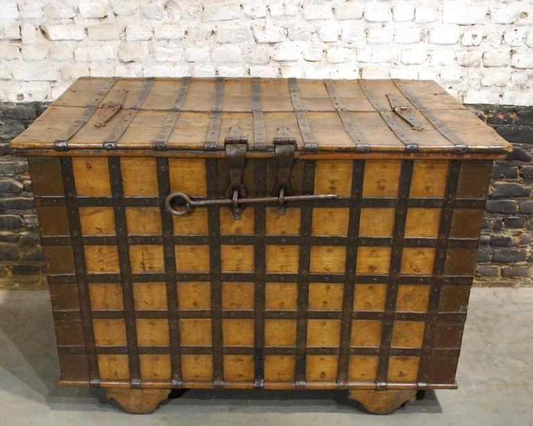 A mid-19th century, Anglo-Indian Trunk with original ribbed iron fittings.  The trunk or chest is made in solid teak wood and richly decorated with hammered and forged iron strappings. It has a hinged top hatch that can be locked by the use of a
