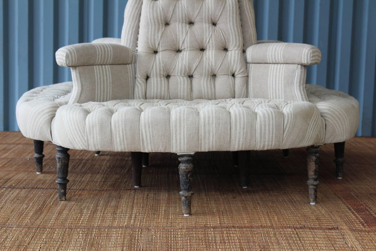 An antique 19th century Napoleon style boudoir sofa, perfect for a dressing room, retail space or foyer. This piece has been completely rebuilt and upholstered in a vintage striped linen. The legs have been kept in their original condition and show