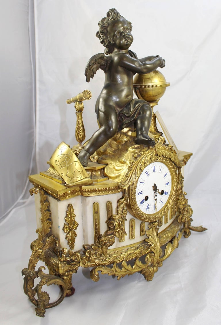 Period  19th century.  Dial  enamel dial with Roman numerals, brass hands, two winding holes, brassouter ring  Decoration  marble body with bronze putti atop, brass globe and telescope. Heavy ornate ormolu mounts to the body, ormolu