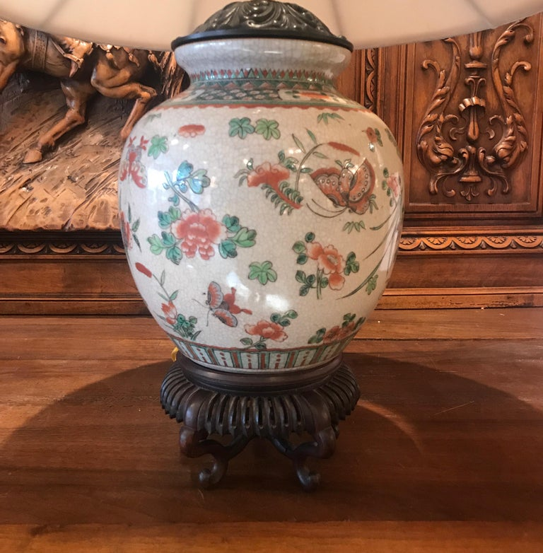 A 19th century hand painted porcelain vase with hand carved rosewood base now as a lamp. This Antique vase was lamped in the first quarter of the 20th century with hand-painted floral decoration with a slight crackles glaze. The base is a