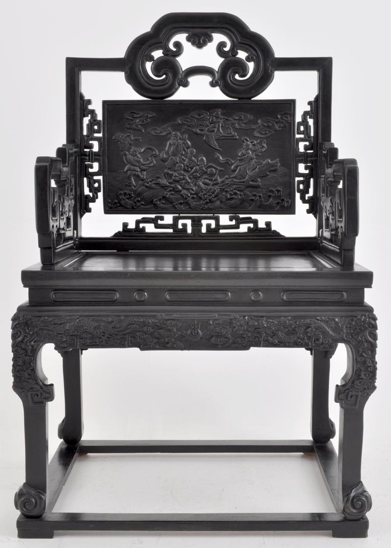 Antique 19th century Chinese Qing Dynasty carved ebonized rosewood chair, circa 1890. The chair having a tablet-shaped backsplat decorated with Chinese immortals in a cloudscape surrounded by mythical beasts. The arms having reticulated and scrolled