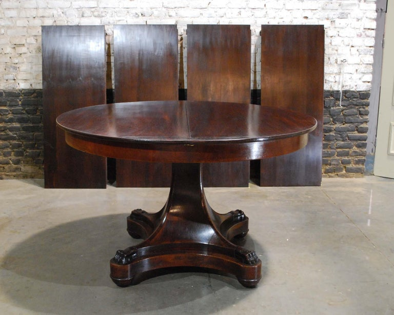 A classic Dutch Empire extension table in beautiful flamed mahogany. The table has a solid mahogany top of 0,63 inches. Below a mahogany veneered apron of 3.15 inches. The top sits on a curved tapered mahogany column that ends in claw feet. The