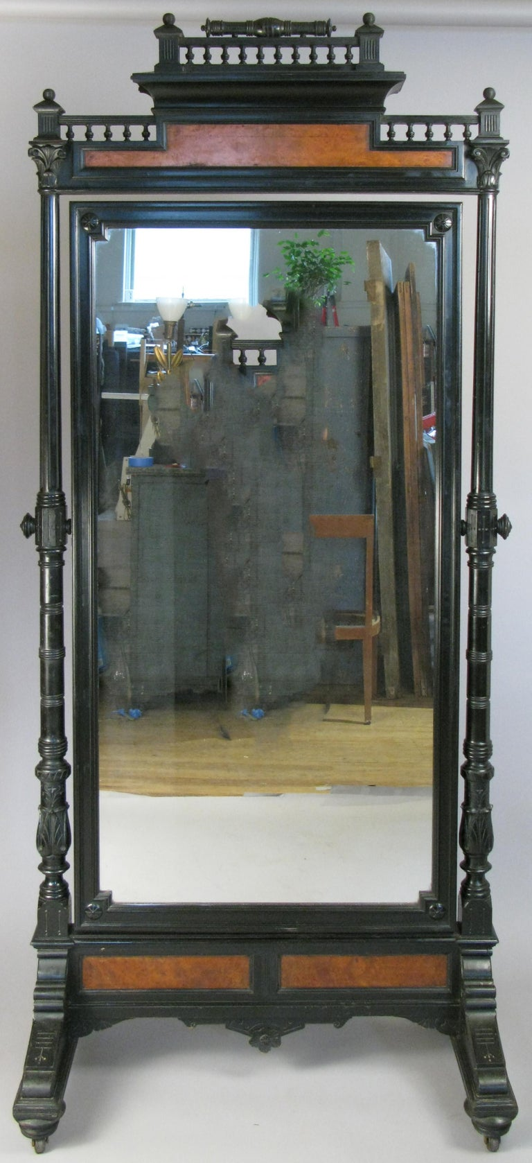 A very handsome 19th century standing cheval mirror, with an ebonized frame and burlwood accents. Beautiful details, design and scale.