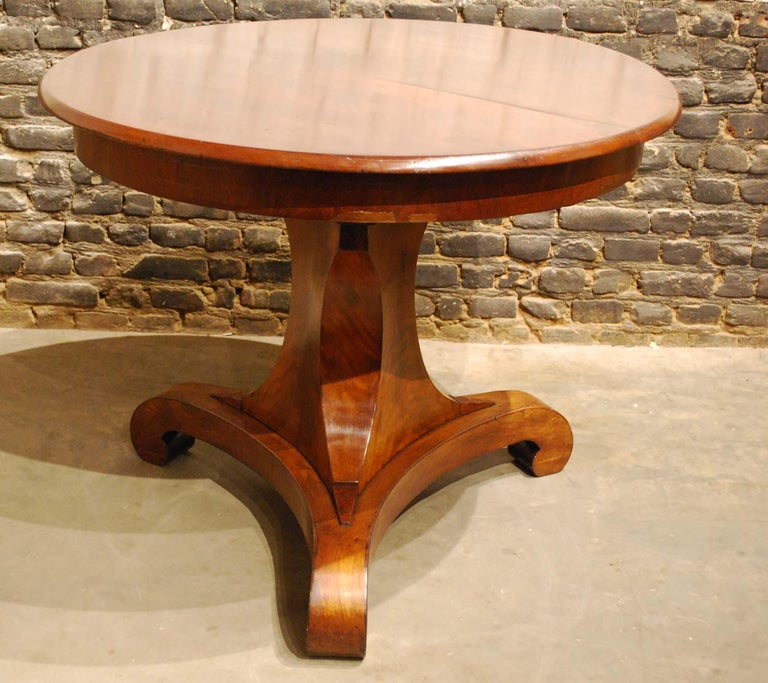 A beautiful round mahogany dining table on a trefoil platform base with facetted edges that end in elegant scrolls. The base has a triangular facetted column made in solid oak and veneered with mahogany and ends in carved feet to support the