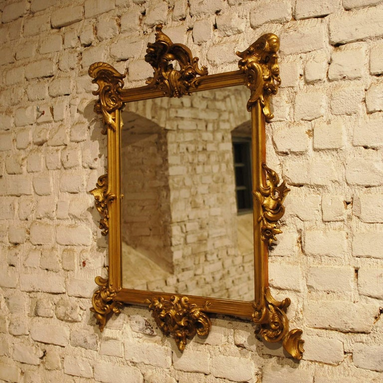 This beautiful rectangular golden mirror is made in France, circa 1870. The frame is decorated with highly detailed baroque ornaments such as C scrolls, acanthus, flowers, and leaves. The Frame has a pine base smoothened with gesso and is partially