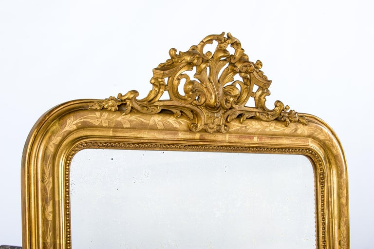 This beautiful antique mirror was made in France around `1890. It is a pure Louis Philippe mirror with its upper rounded corners and elegant frame. The most elevated part of the frame has a floral engraving and a classic pearl beading surrounds the