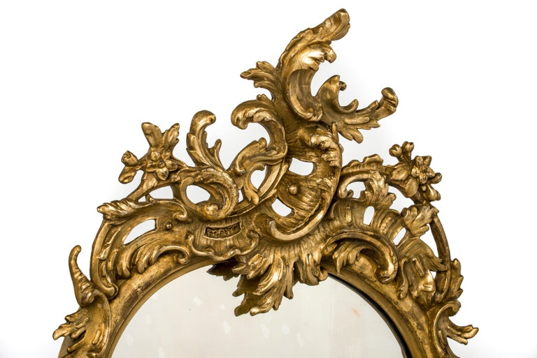 This beautiful abundant ornamented French mirror was made in the late 19th century. Its serpentine shape was made in solid pine smoothened with gesso. The frame is completely decorated with classic French ornaments such as C scrolls, flowers,