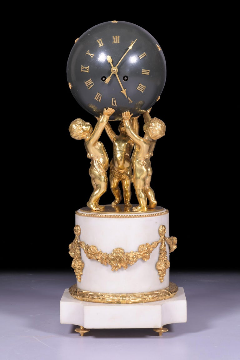 A magnificent & most unusual French marble figural globe clock, the spherical shaped case forming the dial with applied Roman numerals, and arrow hands supported by three dancing putti on cylindrical half column pedestal with applied ribbon tied
