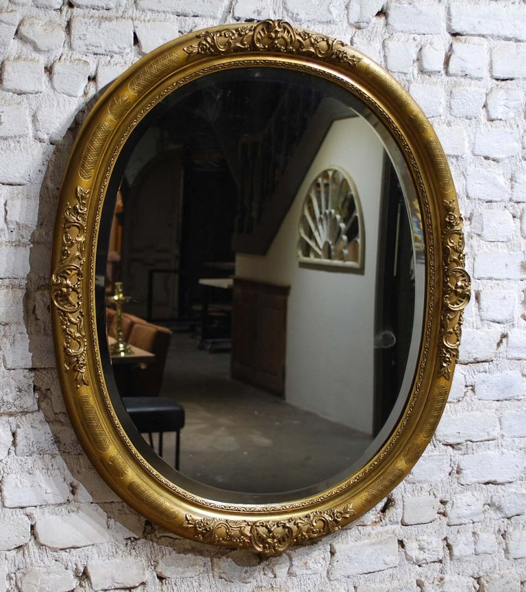 A beautiful antique French oval mirror that was made in France, circa 1890.  The mirror frame is adorned with highly detailed ornaments that depict scrolls, acanthus, flowers, and leaves.  The most elevated part of the frame has floral and cross