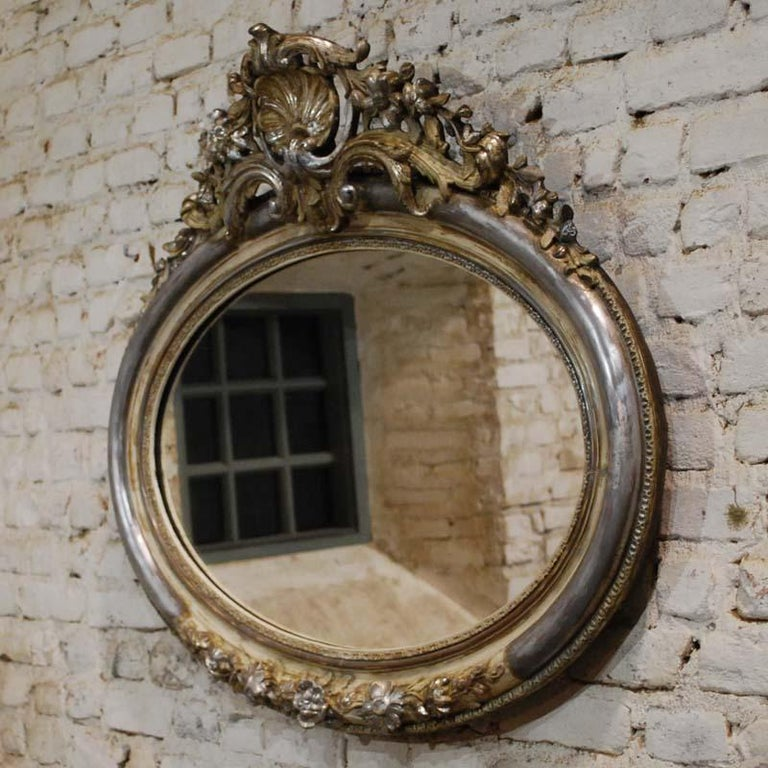 This beautiful oval mirror is partially silver leaf gilt. It has remnants of gold paint and it shows the bone color of the gesso.