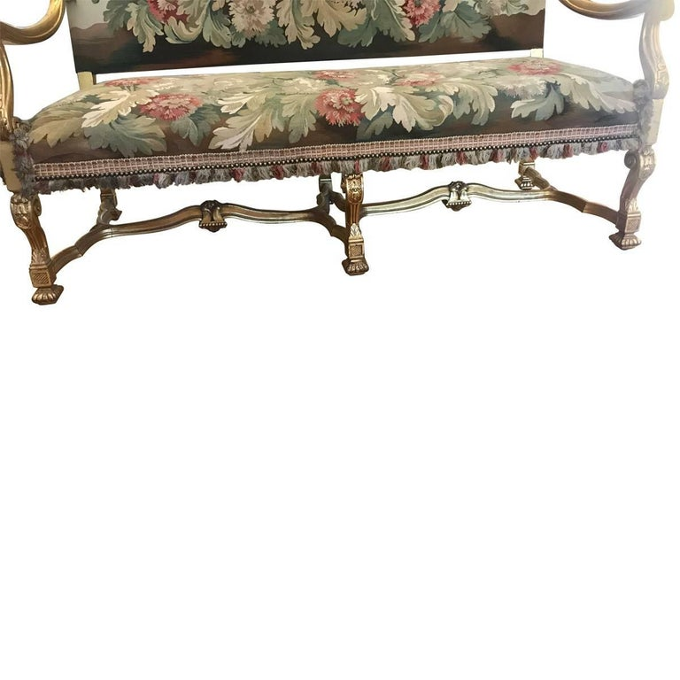 A collectible piece from bygone days, featuring the finest craftsmanship, materials, and design elements of its given era. Elegant and ornate, this stunning settee features a hand-carved giltwood frame and tapestry-style upholstery. Made in France