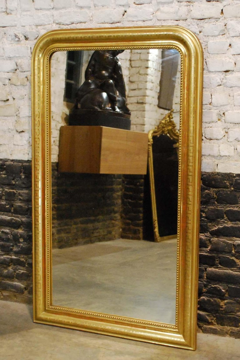 A beautiful gold leaf gilt French mirror. It has the upper rounded corners typical for the Louis Philippe style. The mirror frame has an elegant pearl beading surrounding the glass. The most elevated part Is engraved with a Classic geometric Greek