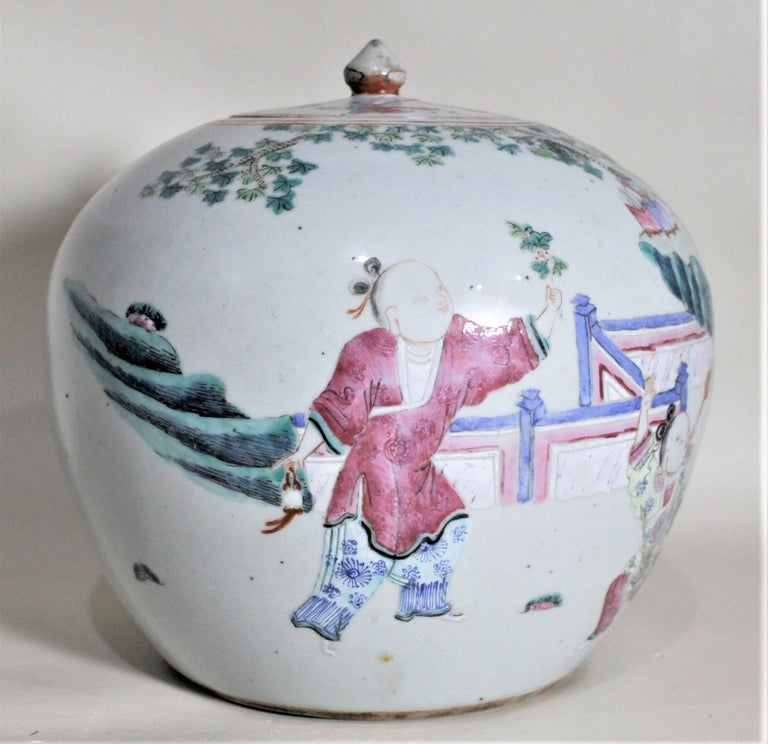 This rather large antique Asian covered jar is unmarked but believed to have been made in China in circa 1880 for the export market. The jar is done with a robin egg blue background with hand painted vignettes around the perimeter with cherry