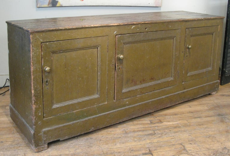 A beautiful late 19th century large three door Italian mercantile cabinet, in its original dark green painted finish and brass hardware. wonderful scale and character.