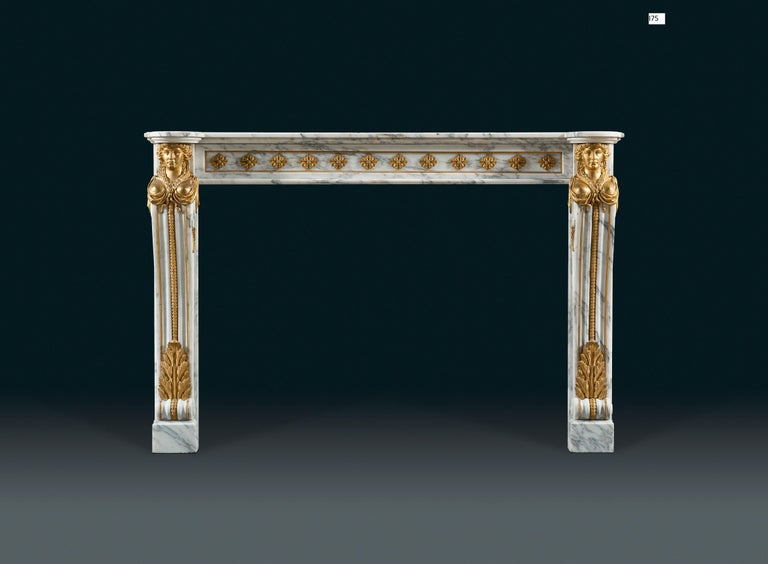 A 19th century, Louis XVI style chimneypiece in veined statuary marble with impressive and well-cast gilt bronze mounts. The rectangular shelf with rounded ends. The frieze with well-cast ormolu flower heads applied to the marble frame, the console
