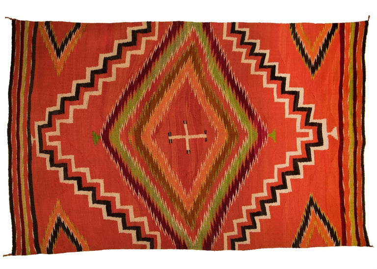 A vintage 19th century Navajo Textile in a wearing blanket format with a soft, fine weave of native hand-spun wool in aniline red, orange and green with natural fleece colors of ivory and brown/black. A central cross is surrounded by diamond