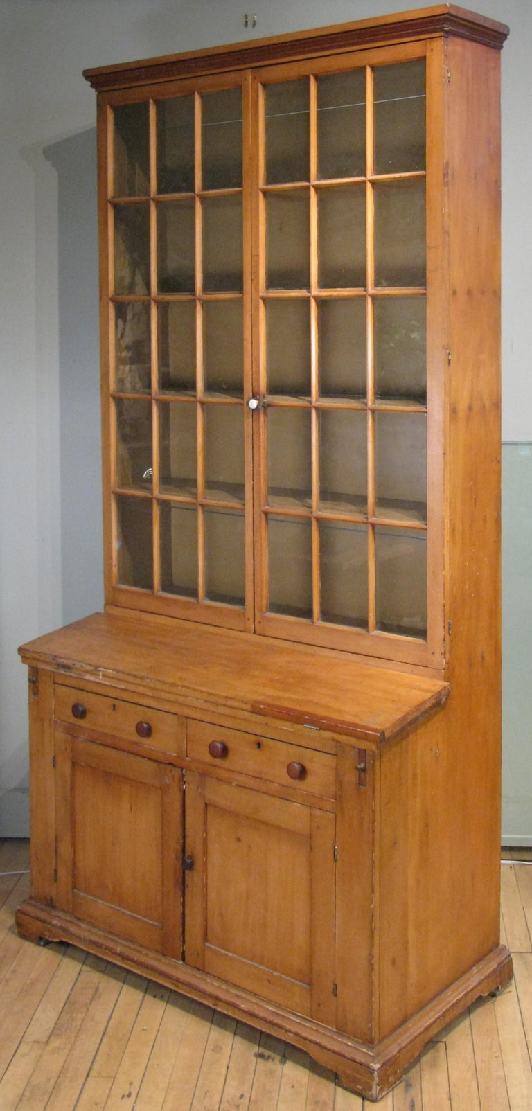 A very handsome antique late 19th century secretary bookcase with a fold out desk surface. Upper section has a pair of divided pane glass doors with shelves, and the lower portion has two drawers and a pair of doors with shelf. Very nice scale and