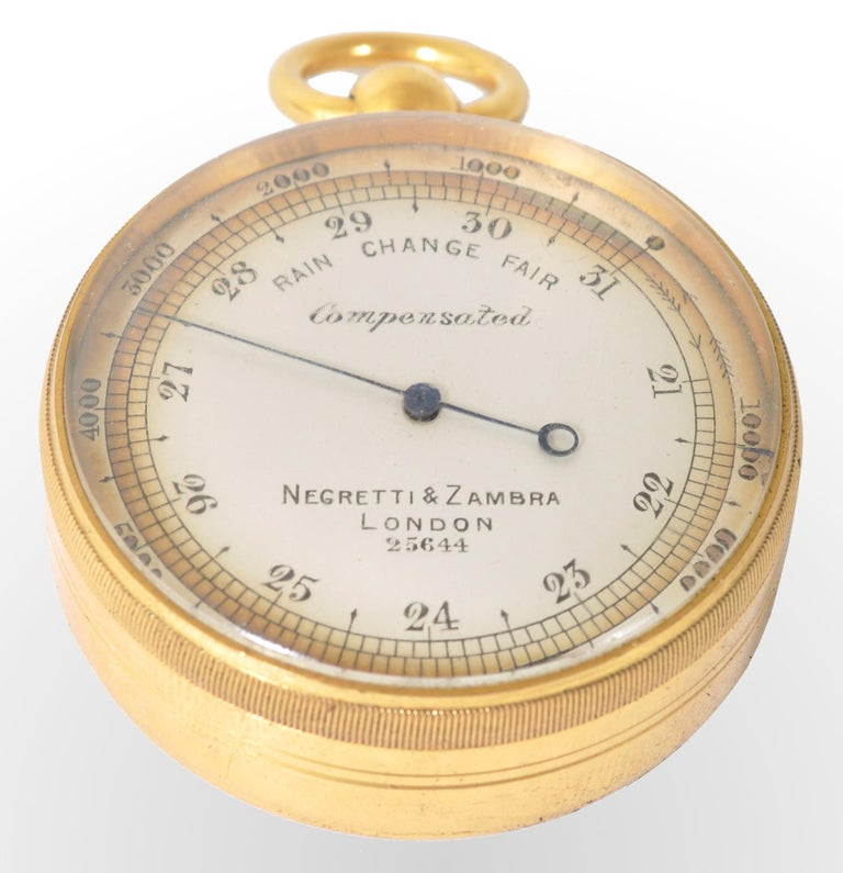 Antique 19th century pocket barometer by Negretti & Zambra of London, circa 1880. The barometer in a gilded metal case with a white enamel dial. The barometer housed in the original outer sharkskin case.