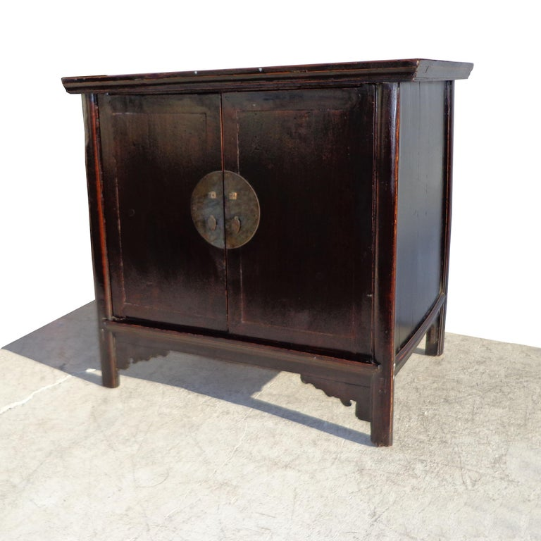 Created in China during the Qing Dynasty, this cabinet features two doors, fitted with a bronze medallion. Four straight legs with carved apron in the front. Beautiful patina in dark elm finish with red undertones.