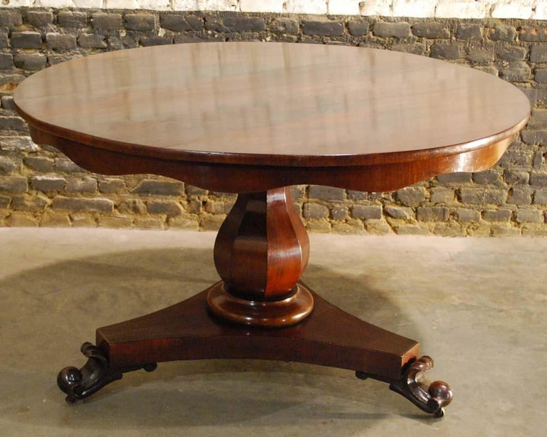 """A beautiful round mahogany dining table on a trefoil platform base that ends in elegant handcarved scrolls. The base supports an octagonal baluster in mahogany veneer. The table top is made with mahogany veneer in """"livre ouvert"""" style. It is made"""
