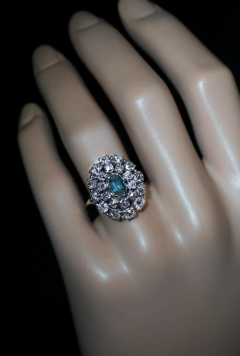 Circa 1870  This antique Victorian era cluster ring is finely crafted in 14K gold and silver. The ring is centered with a rare Russian Alexandrite (6.55 x 3.99 x 3.50 mm, approximately 0.75 ct), surrounded by two rows of chunky old mine cut