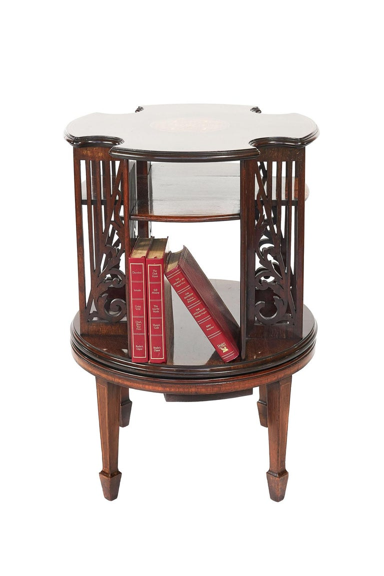 Antique 19th century Sheraton revival inlaid mahogany revolving bookcase having an attractive mahogany shaped top with pretty satinwood centre inlay depicting bell flowers, petals, foliage & urns and double boxwood line inlay to the edges, four