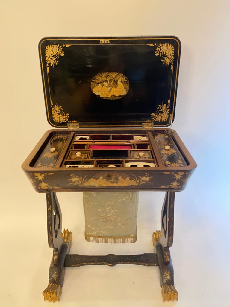Antique 19th century small Chinese lacquer sewing table with hand painted scenes and beautiful legs. Gilt export black lacquer all-over the table.