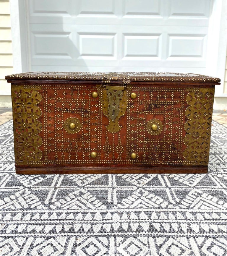Rare 19th century handcrafted Zanzibar chest with brass metal overlay and brass mounts. The antique trunk is comprised of solid carved teak and hardwood and features ornamental hinged lid. The interior is fitted with a candle box on the upper right