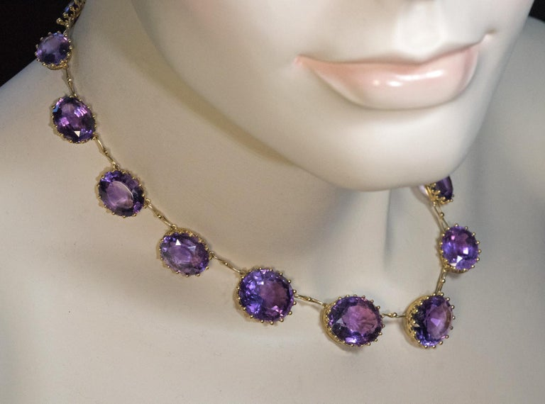 Circa 1890  This antique Victorian era 14K yellow gold necklace features graduating oval cut medium purple amethysts set in royal crown style gold heads.  Length 38 cm (15 in.)