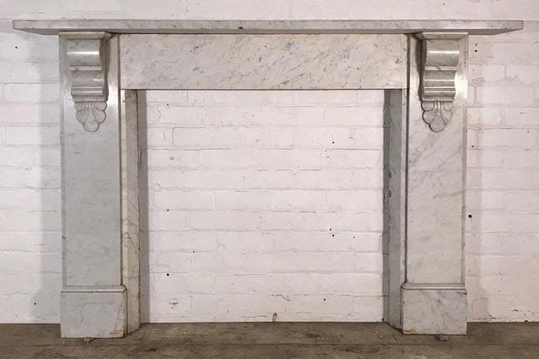 Antique 19th century Victorian Carrara marble fireplace surround with carved corbels supporting the shelf, and chamfered inside returns, circa 1870.   This fireplace is currently unrestored and these images reflect its current condition. It has