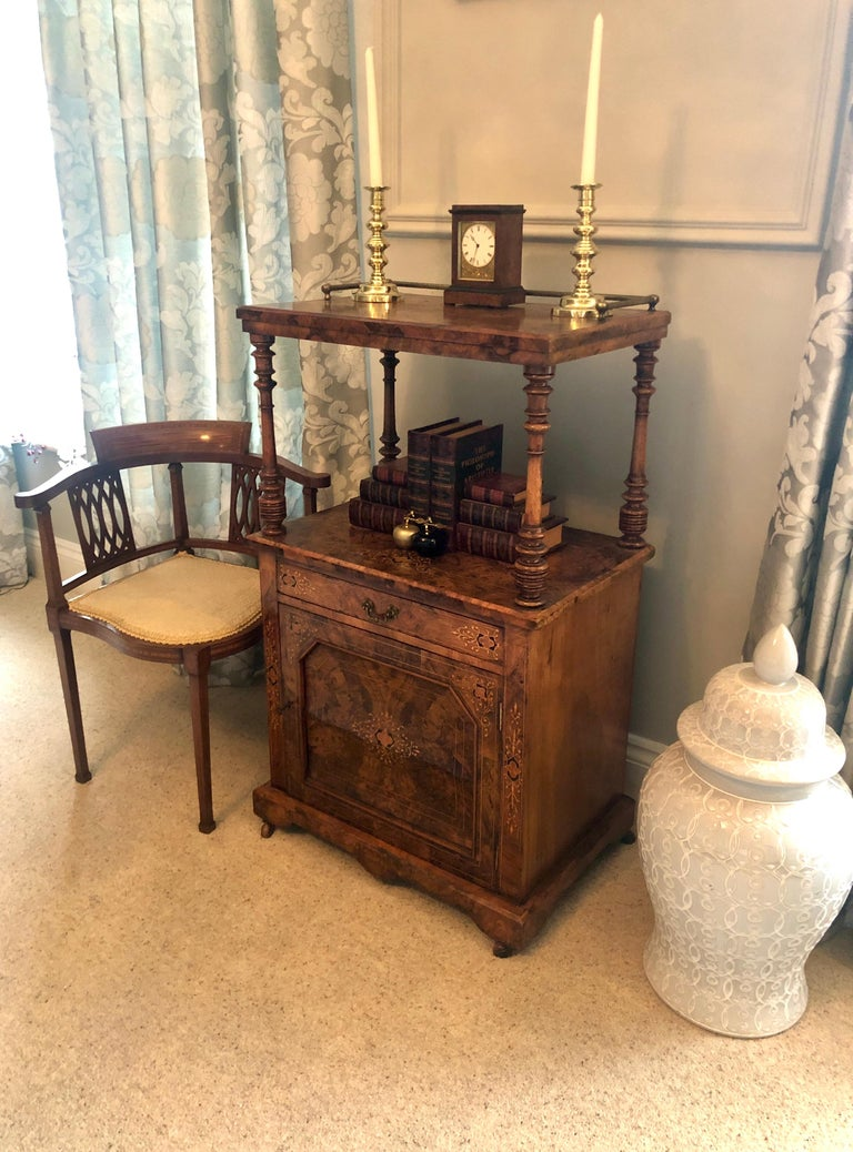 Quality antique Victorian inlaid burr walnut Canterbury with original brass gallery. The inlaid burr walnut top is outstanding. It has four elegantly turned columns supports, one-drawer with original brass handle, one inlaid burr walnut door opens