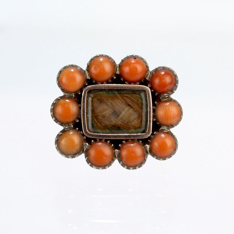 A wonderful, diminutive Georgian or early Victorian gold-filled and woven hair brooch or pin.  With braided hair behind glass set in a gold-filled setting surrounded by small pink coral cabochons.   In the Georgian and Victorian eras, woven hair art