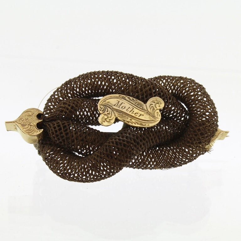 A good late Georgian or Victorian memorial hair art brooch.  Comprised of an interlocking double looped knot of woven hair mounted with a central scroll-shaped cartouche engraved with the dedication that reads