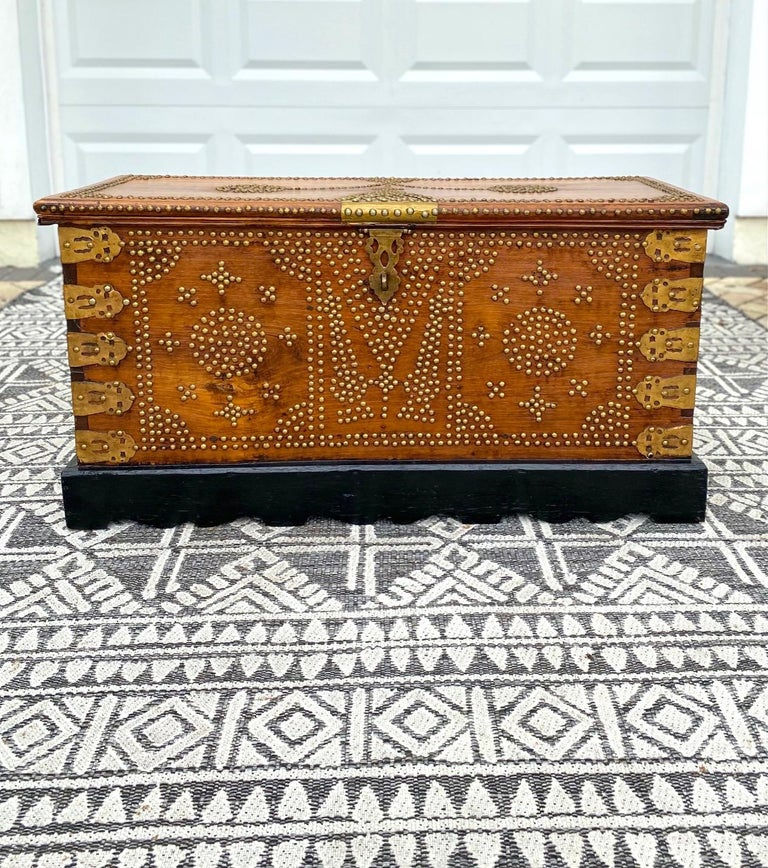 Rare 19th century handcrafted Zanzibar blanket chest with brass metal overlay and brass studs throughout. The antique trunk is comprised of solid carved teak wood and features ornate brass interior hinges. The interior is also fitted with a candle