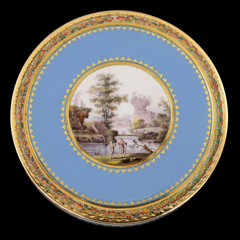 Antique early 19th century Swiss 18-karat gold bonbonniere box, the lid set with a round enamel panel painted on white ground depicting two gentleman looking at a countryside landscape, within a fine gilt leaf frame, surrounded by translucent blue