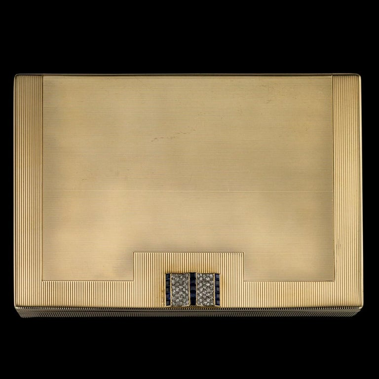 Antique 20th century Cartier Art Deco 9 carat gold extremely large compact, of rectangular form, inside bearing various open and closed compartments and a retracting lipstick, the top lid mounted with a sliding push-button, set with brilliant cut