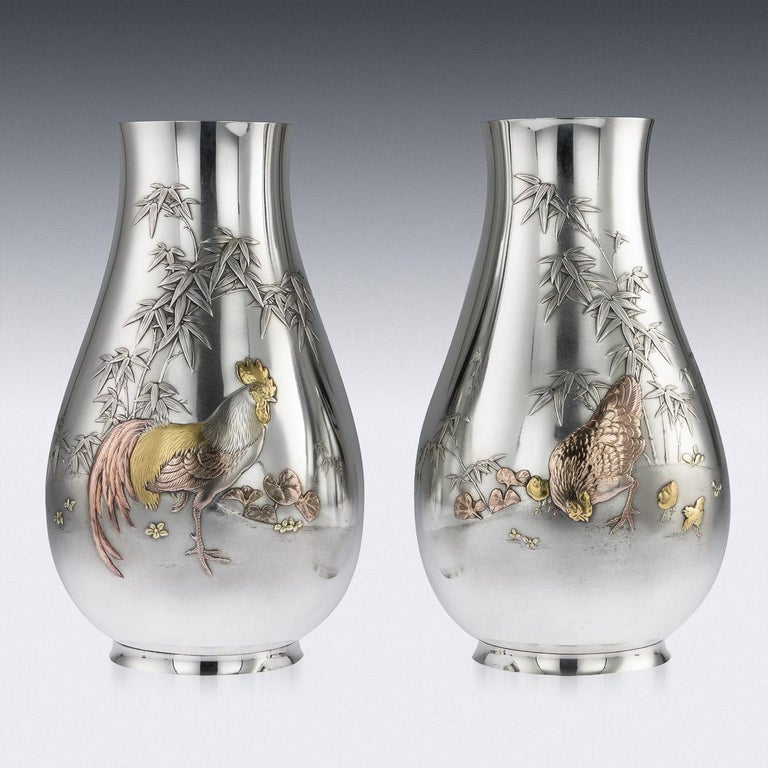 Antique early-20th century Japanese Meiji period solid silver and mixed-metal pair of vases. The bulbous body chased and applied with a rooster, chicken and baby chicks, flowering bamboo branches with copper, gold and gilt details, the pair features