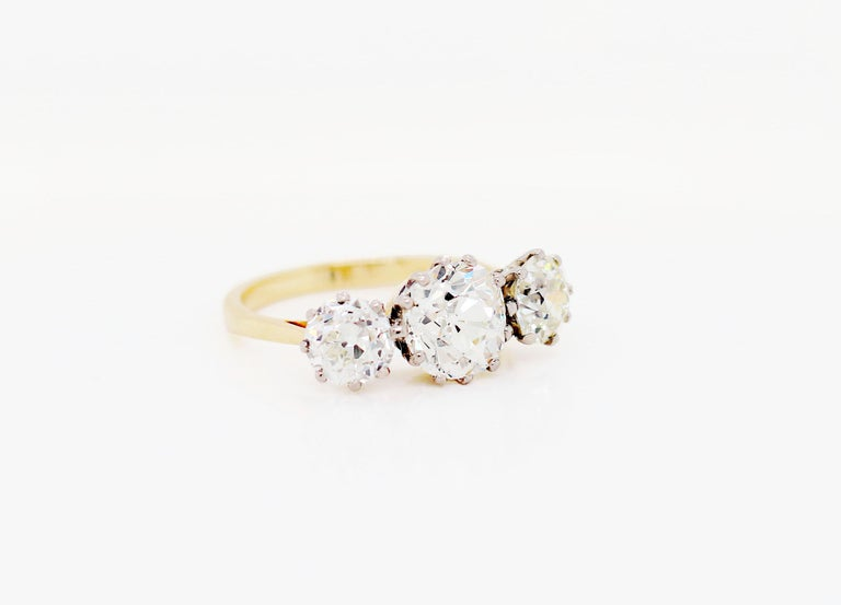 Exquisite antique three stone engagement ring featuring a cushion shaped old cut diamond in the centre weighing 2.50ct mounted in a 12 claw open back setting. The centre stone is accompanied by two round old cut diamonds on either side weighing