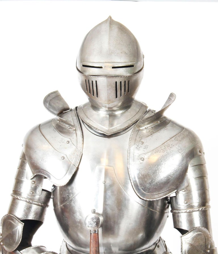 This is a fabulous antique handcrafted complete suit of life-size Greenwich style Tudor Knight plate armour dating from the early 20th century.  The finely cast fully articulated suit is mounted on a wooden Stand with an upholstered mannequin and