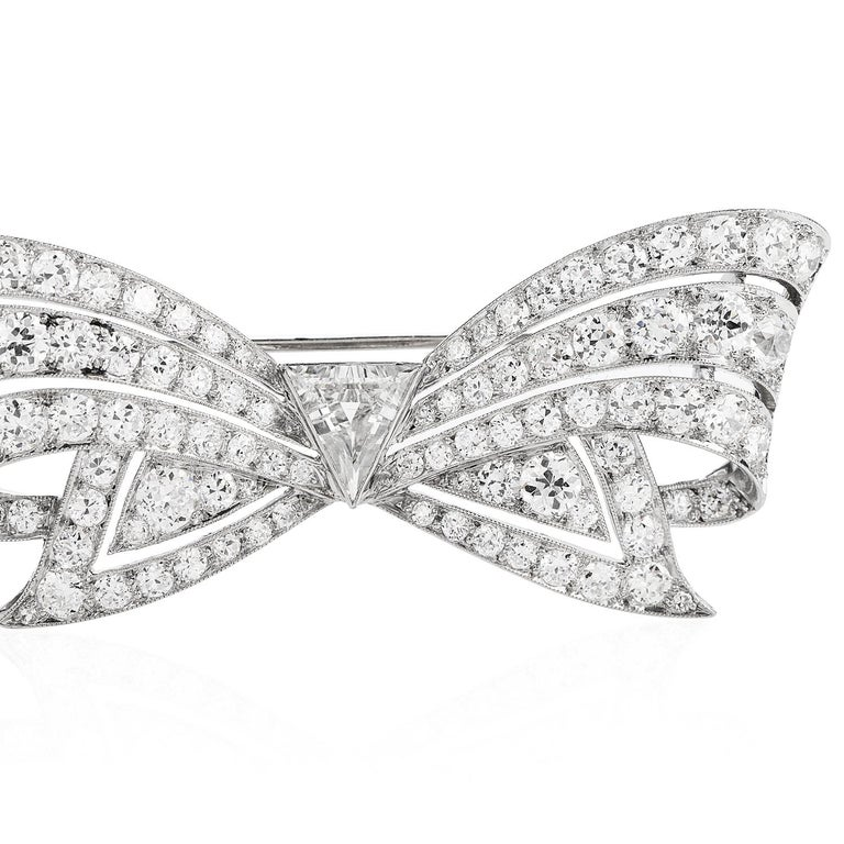 This stunning Antique1930's diamond brooch Pin handcrafted in Platinum. This sparkling broochpin features a bow design centered with a triangular natural diamond weighing approx. (0.85, H-I color and VS clarity) bezel-set.  It is surrounded