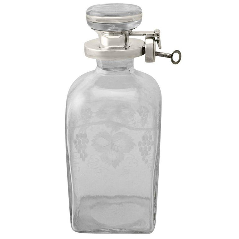 A fine and impressive antique George V English acid etched glass and sterling silver mounted locking decanter; an addition to our antique lounge collection.  This exceptional antique George V glass and sterling silver mounted decanter has a