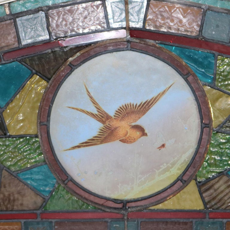 An antique Aesthetic Movement mosaic transom window features leaded stained and jeweled glass design with central medallion having hand painted bird (Swallow) and insect in flight, circa 1870  Measures: 19