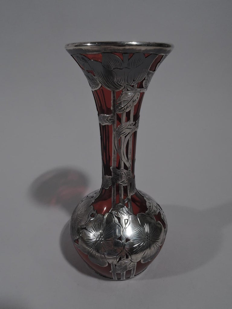 Turn-of-the-century Art Nouveau red glass bud vase with engraved silver overlay. Ovoid bowl with tall cylindrical neck and flared mouth. Vertical trellis groups entwined with stems and leaves, and flower heads at rim and bowl shoulder. Round