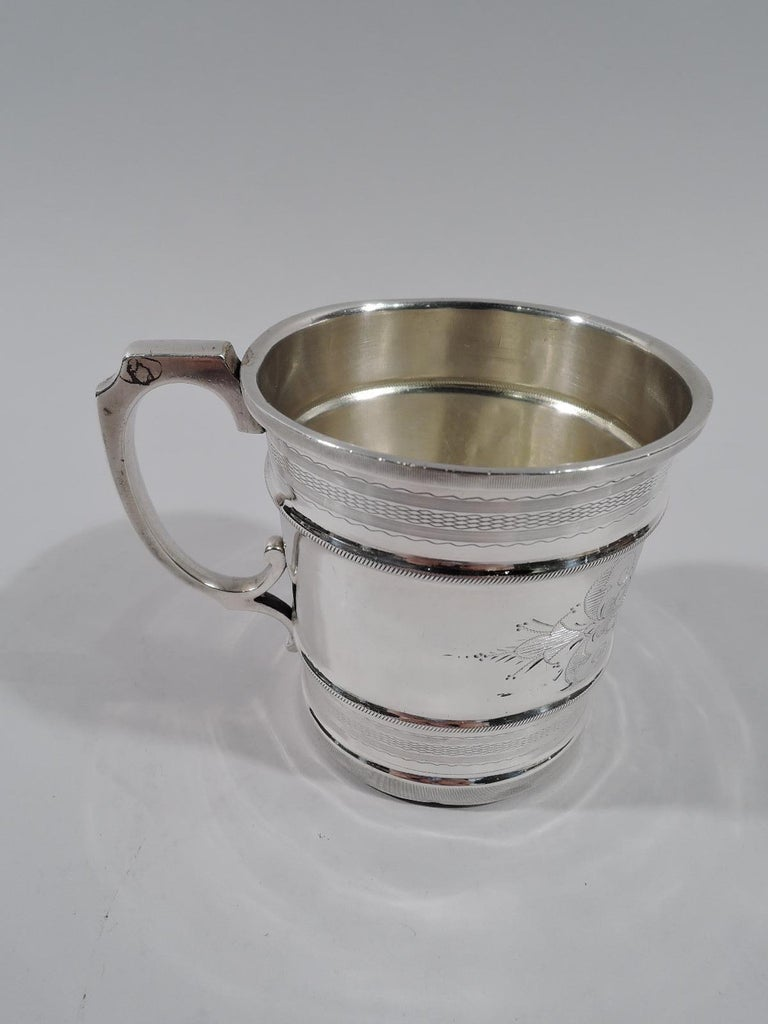 Aesthetic coin silver baby cup. Made by Juergens & Andersen in Chicago. Straight sides with ribbed rim and base. Two cabled girdles frame central shaped cartouche (vacant) between stylized leafy scrolls. At top and bottom ornamental wavy and linear