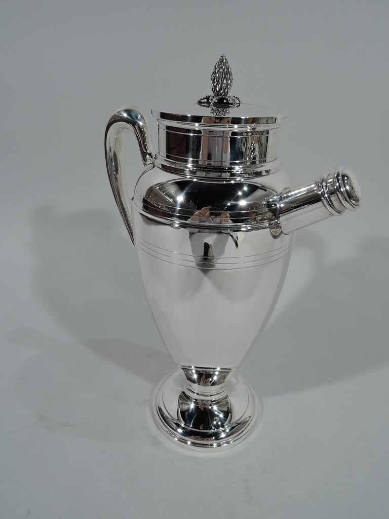 Art Deco sterling silver cocktail shaker. Made by Redlich Ovoid body, stepped and domed foot, high-looping scroll handle, and straight and stubby spout with built-in strainer and threaded cap. Short neck with flat cover surmounted by pineapple