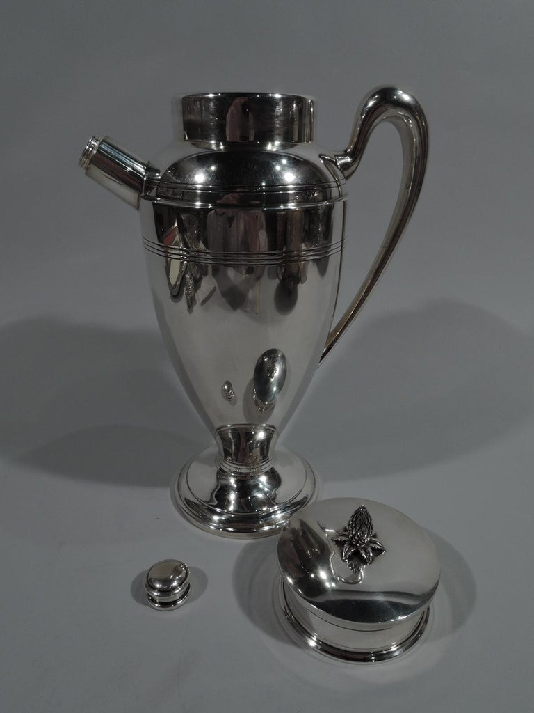 Art Deco sterling silver cocktail shaker. Made by Redlich in New York, ca 1925. Ovoid body, stepped and domed foot, high-looping scroll handle, and straight and stubby spout with built-in strainer and threaded cap. Short neck with flat cover