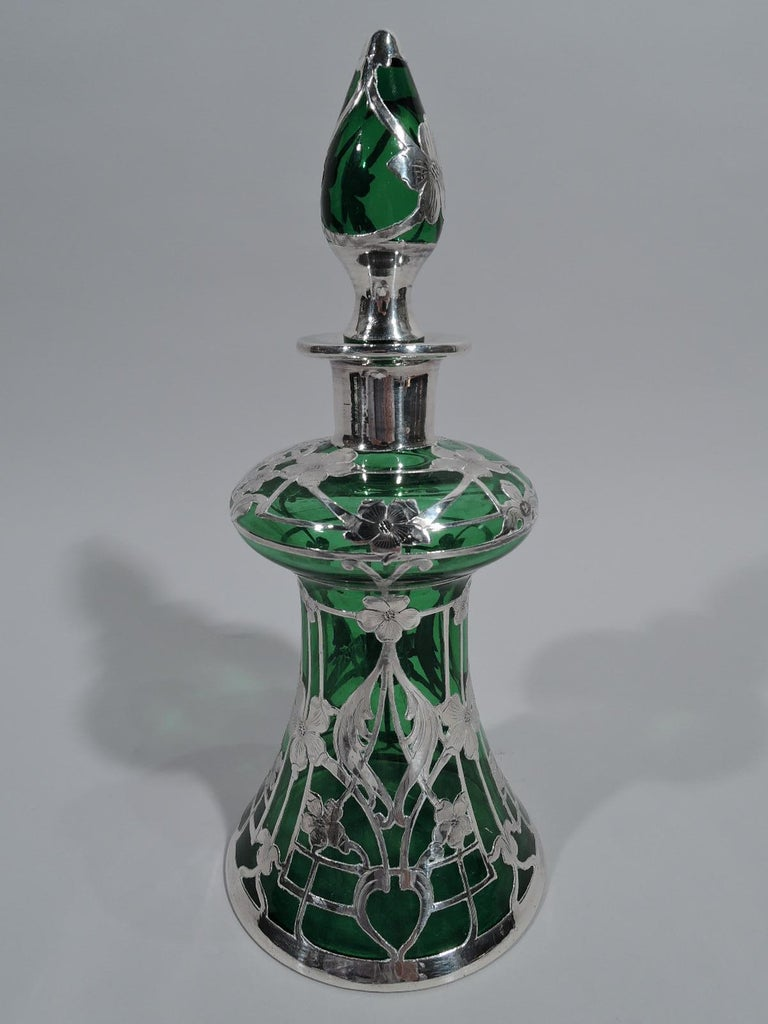 Turn of the century Art Nouveau glass decanter with engraved silver overlay. Unusual form with conical body, bellied top, straight and inset neck, and flat everted rim. Stopper oval. Overlay in form of rectilinear trellis with flower heads and