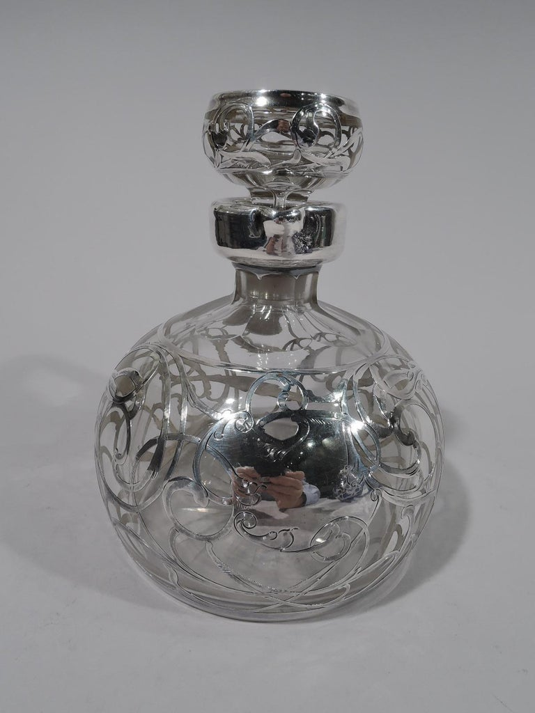 American Art Nouveau clear glass jug decanter with silver overlay, circa 1910. Globular with short faceted neck and bracket handle. Stopper flat topped with short plug. Rolling and entwined engraved silver scrollwork with leaves. Asymmetrical