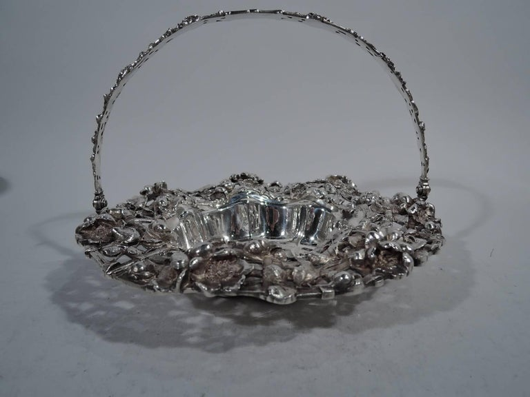 Art Nouveau sterling silver basket. Made by Dominick & Haff in New York in 1902. Plain scalloped well engraved with shaded monogram. Rim wide open trellis interwoven with flowers. C-scroll wing handle same with central oval frame (vacant). Pretty